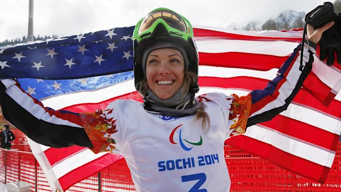 Amy Purdy of United States celebrates her 3rd place in the women's para snowboard cross, standing event at the 2014 Winter Paralympic, Friday, March 14, 2014, in Krasnaya Polyana, Russia. (AP Photo/Dmitry Lovetsky)