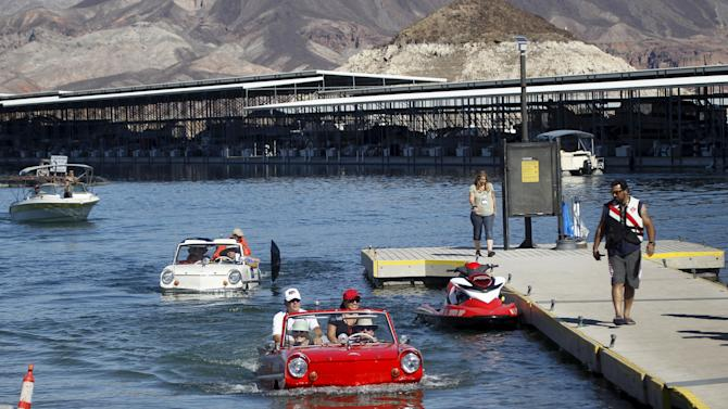 A 1965 Amphicar driven by Dean Baker of Lake Havasu, Arizona, and a 1963 Amphicar, driven by Rob Vondracek of Fountain Hills, Arizona, drive out of Lake Mead during the first Las Vegas Amphicar Swim-in at Lake Mead near Las Vegas