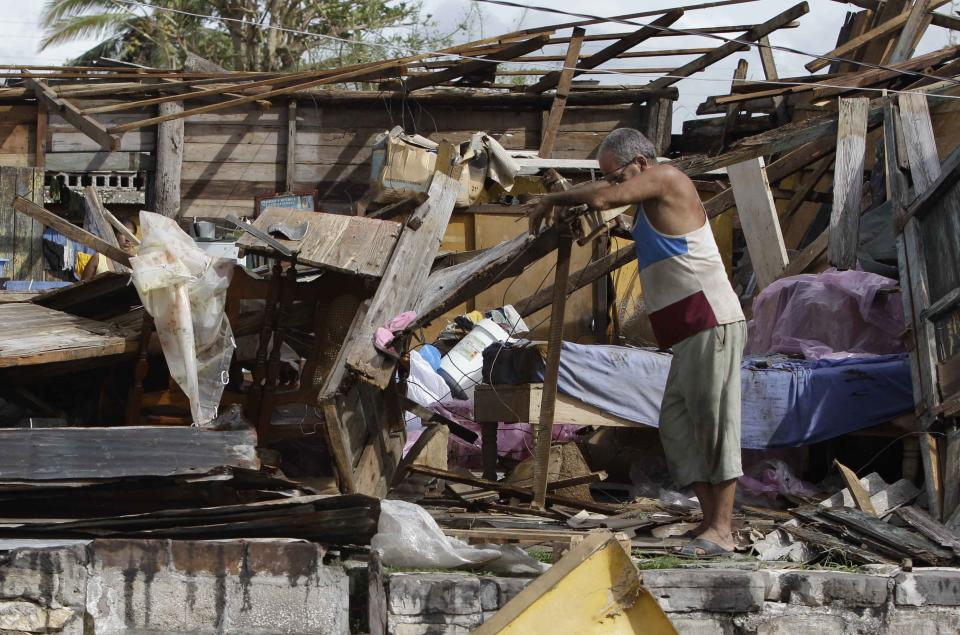 Resident Antonio Garces tries to recover his belongings from his house destroyed by Hurricane Sandy in Aguacate, Cuba, Thursday Oct. 25, 2012. Hurricane Sandy blasted across eastern Cuba on Thursday as a potent Category 2 storm and headed for the Bahamas after causing at least two deaths in the Caribbean. (AP Photo/Franklin Reyes)