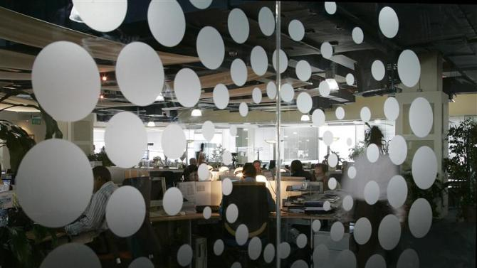 New Thomson Reuters logo is seen as employees sit at their desks in the Dubai office
