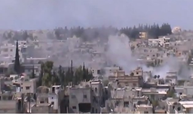 In this image taken from video obtained from the Shaam News Network, which has been authenticated based on its contents and other AP reporting, smoke rises from buildings from heavy shelling in Homs,