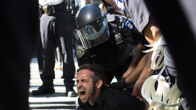 Occupy Wall Street protestor Chris Philips screams as he is arrested near Zuccotti Park, Monday, Sept. 17, 2012, in New York. Multiple Occupy Wall Street protestors have been arrested during a march toward the New York Stock Exchange on the anniversary of the grass-roots movement. (AP Photo/John Minchillo)