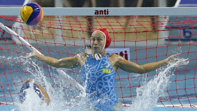 Kazakhstan's goalkeeper Zharkova jumps to block a goal attempt from Japan during their Women's Single Round Robin water polo match at the Dream Park Aquatics Centre during the 17th Asian Games in Incheon