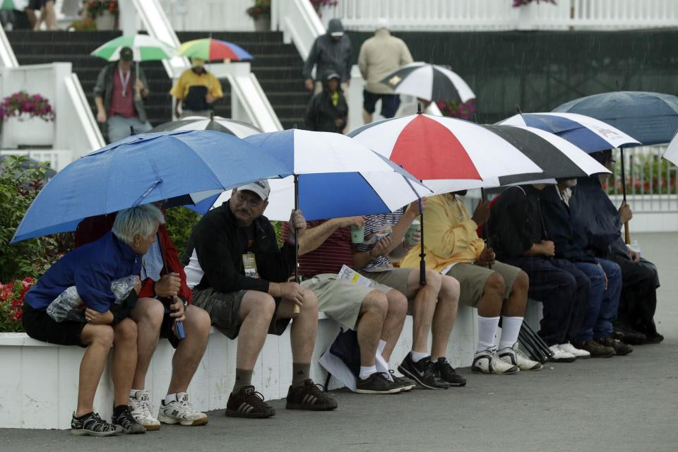 Spectators wait out a weather delay during the first round of the U.S. Open golf tournament at Merion Golf Club, Thursday, June 13, 2013, in Ardmore, Pa. (AP Photo/Gene J. Puskar)