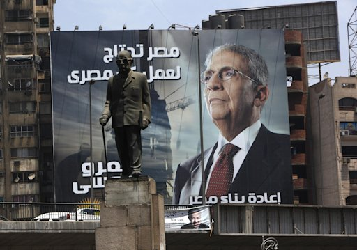 A statue of Egypt's Nobel laureate Naguib Mahfouz is back dropped with an electoral poster of presidential candidate Amr Moussa and Arabic writing which reads,