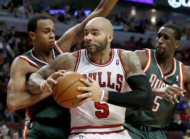 Milwaukee Bucks forward John Henson, left, and forward Ekpe Udoh (5) pressure Chicago Bulls forward Carlos Boozer (5) during the second half of an NBA basketball game Tuesday, Dec. 10, 2013, in Chicag
