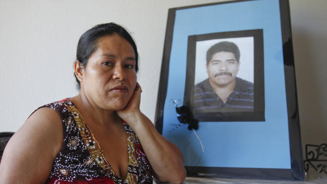 In this June 25, 2012 photo, Juana Garcia Martinez poses next to a photo of Juana Garcia's late husband, Ildefonso Martinez, in Vista, Calif.  Ildefonso Martinez died from dehydration trying to cross back into the United States after being deported last year. The death of migrants crossing the Southwest border has long been a tragic consequence of illegal immigration and many say, the massive increase in U.S. border enforcement. For some, the tragedies are a powerful motivator in pushing Congress to act this year on a larger immigration reform package. (AP Photo/Lenny Ignelzi)