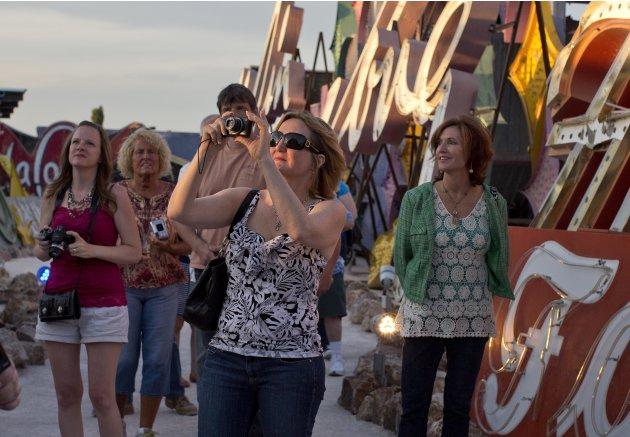 Tourists walk through a display of old hotel and casino signs at sunset at the Neon Museum in Las Vegas on Friday, May 24, 2013. For the past six months, tourists have had to squint up at the hulking
