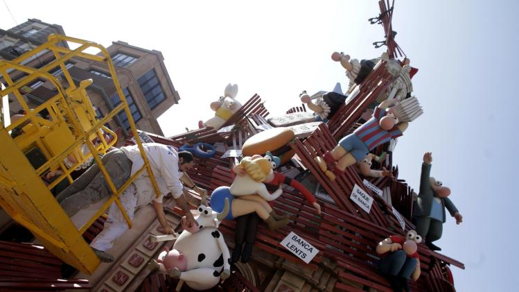 "Craftsmen put finishing touches on a monument at the start of the ""Fallas"" festival in Valencia"