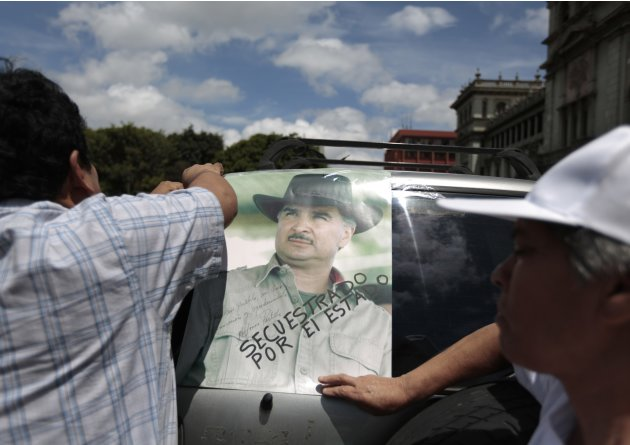 Supporters of former Guatemalan President Portillo, stick a picture of Portillo on a car, in front of the Presidential Palace, in downtown Guatemala City