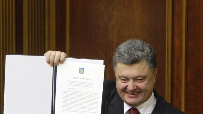 Ukraine's President Poroshenko shows a signed landmark association agreement with the European Union during a session of the parliament in Kiev