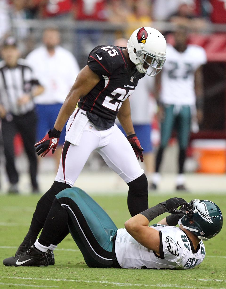 Arizona Cardinals free safety Kerry Rhodes, top, stands over Philadelphia Eagles tight end Brent Celek, bottom, after jarring the ball away from Celeck in the second quarter of an NFL football game on Sunday, Sept. 23, 2012, in Glendale, Ariz. (AP Photo/Paul Connors)
