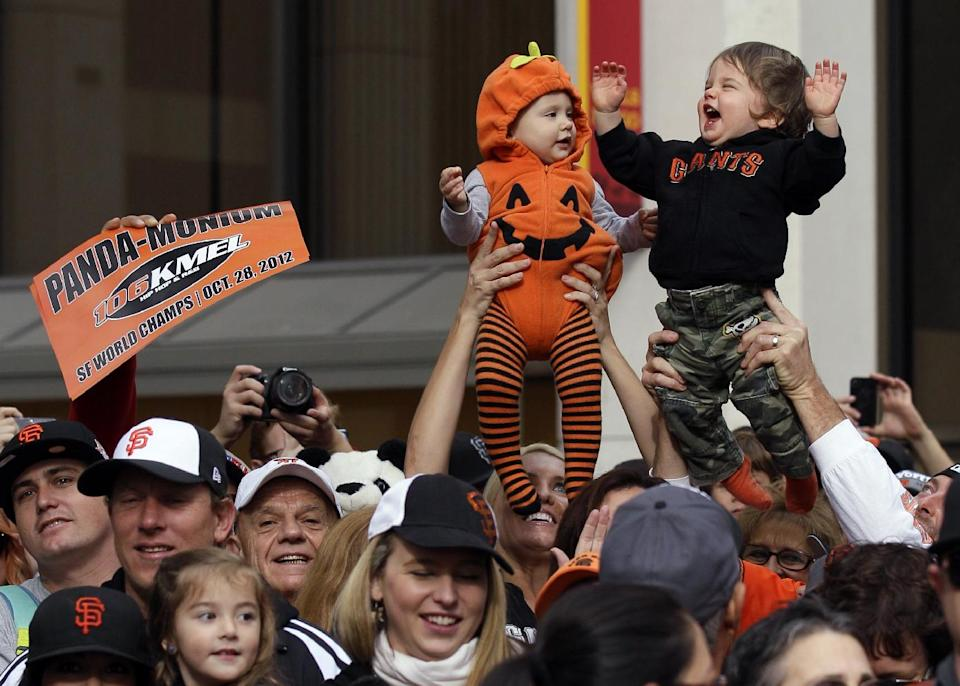 Fans hold up their children, cousins Reagan Hagerstrand, 10-months, and Ryan Magnani, 1, right, during the San Francisco Giants World Series victory parade, Wednesday, Oct. 31, 2012, in San Francisco. (AP Photo/Jeff Chiu)