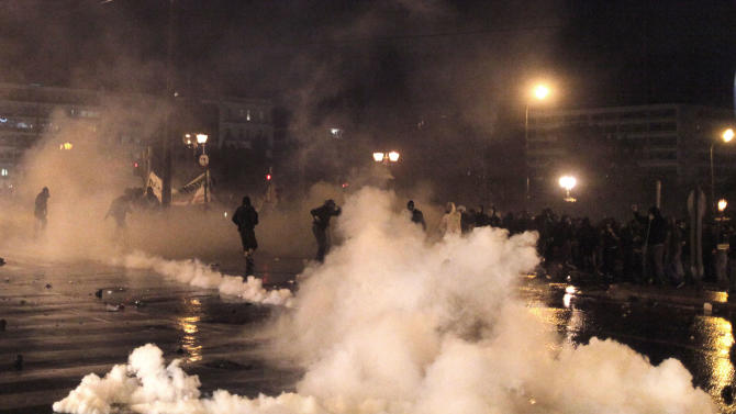 Engulfed by tear gas thrown by police, protesters run for cover during clashes with police, near the parliament in Athens, Wednesday Nov. 7, 2012. Greece's fragile coalition government faces its toughest test so far when lawmakers vote later Wednesday on new austerity measures demanded to keep the country afloat, on the second day of a nationwide general strike. (AP Photo/Petros Giannakouris)
