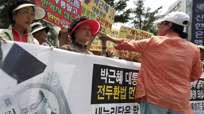 """South Korean protesters stage a rally demanding their government to recover former South Korean President Chun Doo-hwan's slush fund in front of the ruling Saenuri Party headquarters in Seoul, South Korea, Monday, June 24, 2013. Prosecutors are racing against time to collect 167 billion won ($144 million) from Chun's slush fund - a hunt meant to help close one of modern South Korea's darkest chapters. The letters at a banner read: """"President Park Geun-hyun must punish Chun Doo-hwan according the the law."""" (AP Photo/Yonhap, Bae Jung-hyun) KOREA OUT"""