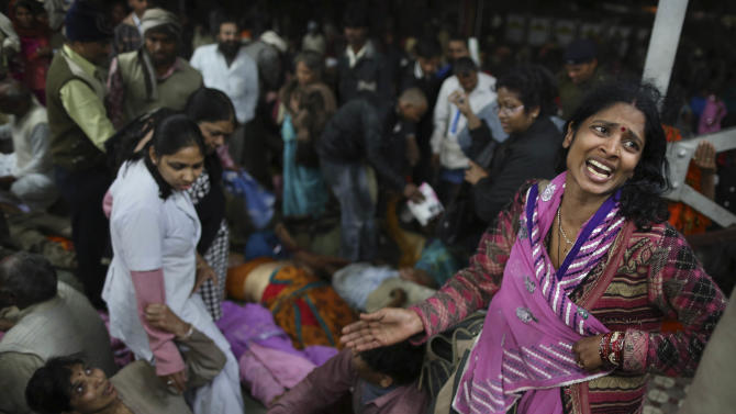 An Indian woman weeps as she and other family members mourn next to the body of a relative who was killed in a stampede on a railway platform at the main railway station in Allahabad, India, Sunday, Feb. 10, 2013. At least ten Hindu pilgrims attending the Kumbh Mela were killed and more then thirty were injured in a stampede on an overcrowded staircase, according to Railway Ministry sources. (AP Photo/Kevin Frayer)