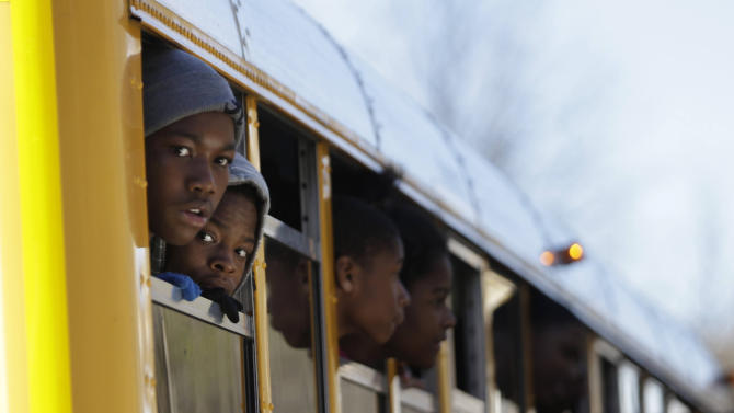 Children look out from a school bus as they are transported to their parents after a shooting at an Price Middle school in Atlanta Thursday, Jan. 31, 2013. A 14-year-old boy was wounded outside the school Thursday afternoon and a fellow student was in custody as a suspect, authorities said. No other students were hurt. (AP Photo/John Bazemore)