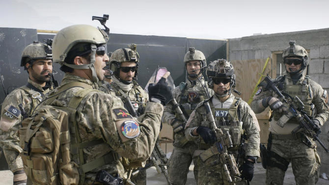 FILE - In this Monday, Jan. 14, 2013 file photo a member of the Afghan special forces, left, briefs soldiers after a training exercise on the outskirts of Kabul, Afghanistan. A senior U.S. commander said Saturday, March 30, 2013 that American special operations forces have handed over their base in eastern Afghanistan's Nirkh district to local Afghan commandos -- meeting a demand by Afghan President Hamid Karzai that U.S. forces withdraw from the district after allegations that their Afghan counterparts committed human rights abuses there. (AP Photo/Musadeq Sadeq, File)