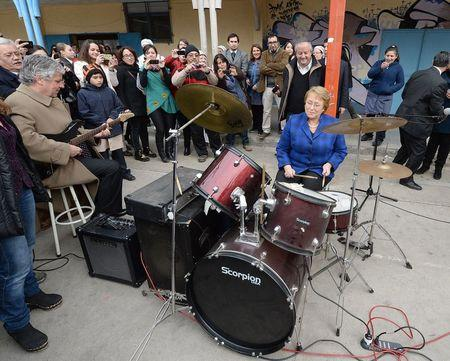 Chile's President Bachelet performs on drums next to Education Minister Eyzaguirreon guitar in a school in Santiago