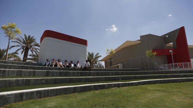 Israeli high-school students sit in the shade provided by a fortified shelter next to a new rocketproof school building, in Shaar Hanegev school, near the southern town of Sderot, Israel, Monday, Aug. 27, 2012. The 27.5 million US Dollar structure features concrete walls, reinforced windows and a unique architectural plan all designed specifically to absorb rocket fire.(AP Photo/Tsafrir Abayov)