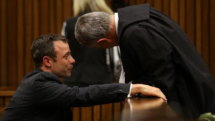 Olympic and Paralympic track star Oscar Pistorius (L) cries as he chats to his lawyer, Barry Roux during a hearing on the sixth day of his trial for the 2013 murder of his girlfriend, on March 10, 2014 at the high court in Pretoria