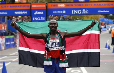 Geoffrey Mutai of Kenya holds up flag after winning the men's division of the New York City Marathon