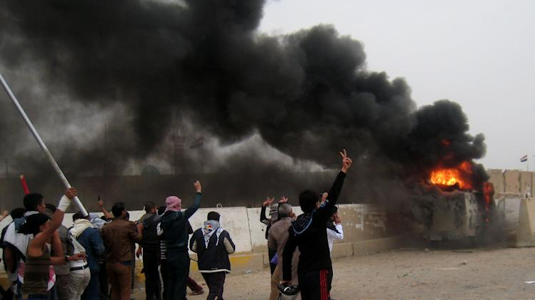 Protesters chant slogans against Iraq's Shiite-led government near a burning Iraqi army armored vehicle during clashes in Fallujah, 40 miles (65 kilometers) west of Baghdad, Iraq, Friday, Jan. 25, 2013. Iraqi troops shot dead five protesters Friday as they opened fire at stone-hurling demonstrators angry at the troops for preventing them from joining an anti-government rally west of Baghdad, officials said. (AP Photo/ Bilal Fawzi)
