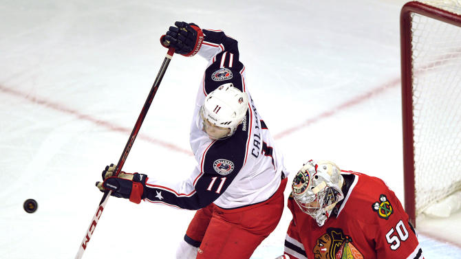 Columbus Blue Jackets' Matt Calvert (11) tries to tip the puck past Chicago Blackhawks goalie Corey Crawford (50) during the first period of an NHL hockey game Sunday, Feb. 24, 2013, in Chicago. (AP Photo/Jim Prisching)