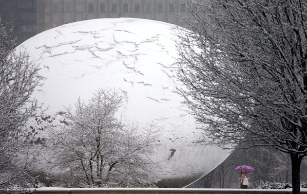"Fresh snow covers Anish Kapoor's sculpture ""Cloud Gate"" and gives it the appearance of a cracked egg as a lone pedestrian walks around the stainless steel attraction in Chicago's Millennium Park, as a winter storm of rain and snow begins Tuesday, Feb. 26, 2013. Forecasters expect the storm to leave behind three to six inches of snow in the greater Chicago area. (AP Photo/Charles Rex Arbogast)"