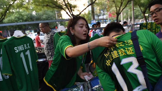 A vendor sells clothing in the colors of the Beijing Guoan football team, outside the Workers Stadium in Beijing, on June 20, 2015