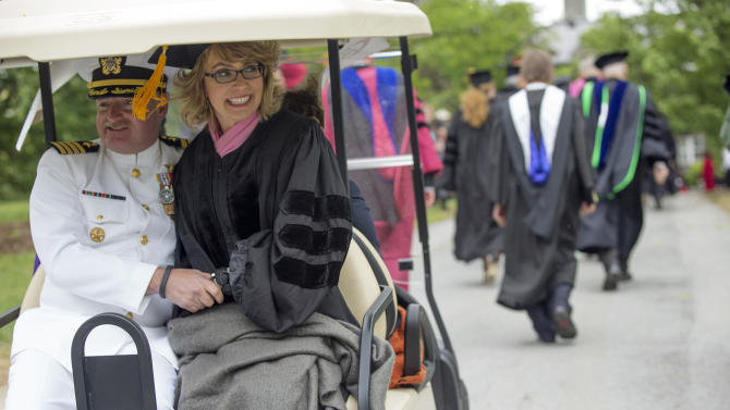 Former U.S. Rep. Gabrielle Giffords and her husband, Mark Kelly, retired space shuttle commander, ride in the procession for the 153rd Commencement at Bard College, Saturday, May 25, 2013, in Annandale-on-Hudson, N.Y. They delivered the commencement address, and Giffords received an honorary degree. (AP Photo/Philip Kamrass)