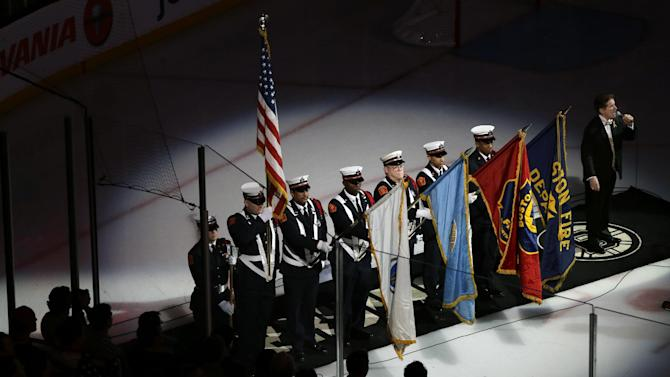 Members of a Boston Fire Department honor guard hold flags during the singing of the national anthem at TD Garden in Boston, Wednesday, April 17, 2013, during a pregame ceremony in the aftermath of Monday's Boston Marathon bombings. (AP Photo/Elise Amendola)