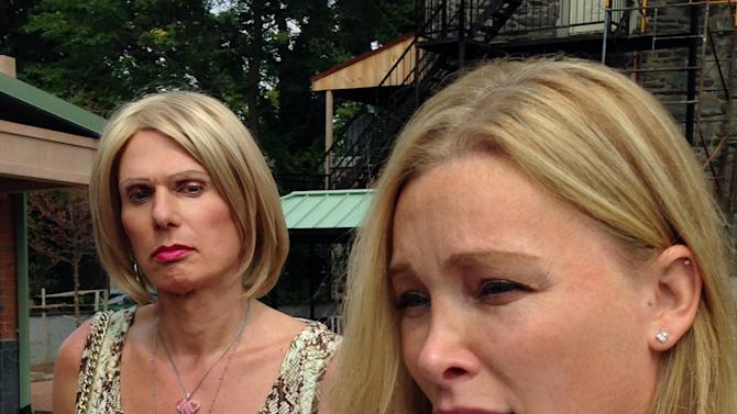Christine Kitzler, left, a transgender woman from Myrtle Beach, S.C., looks on as her surgeon, Dr. Christine McGinn talks to reporters. speaks with reporters, Wednesday, Sept. 2, 2015, in Doylestown, Pa.  A judge has temporarily blocked Kitzler's gender-reassignment surgery for, while he considers her parents' request she be declared incompetent. (AP Photo/Michael R. Sisak)