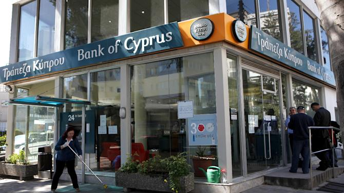 A woman sweeps as people, right, wait outside a branch of Bank of Cyprus in Nicosia, Cyprus, Thursday, March 28, 2013. Bank branches across the country were being replenished with cash, and are scheduled to open for six hours at noon (10:00 GMT). Systems were frozen pending the official noon opening, and guards from a private security firm were reinforcing police outside some ATMs and banks in Nicosia. (AP Photo/Petros Karadjias)