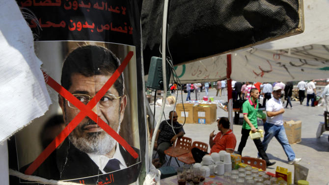 """A poster showing Egypt's ousted President Mohammed Morsi with Arabic slogan reading, """"no revenge without trials,"""" hangs in a popular coffee shop in Tahrir Square in Cairo, Egypt, Tuesday, Aug. 27, 2013. The current bout of violence is the worst in Egypt's 2 ½ years of turbulent transition. It was set off when security forces backed by snipers and armored vehicles broke up two sprawling pro-Morsi protest camps on Aug. 14. More than 1,000 people, most Morsi supporters, were killed in the raids and other violence over the next several days.(AP Photo/Amr Nabil)"""
