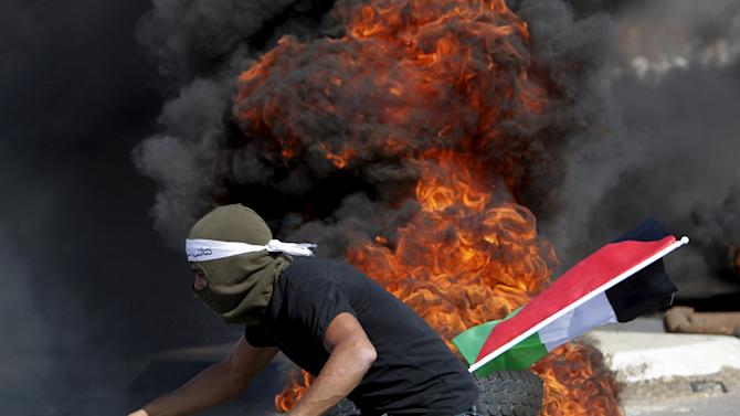Palestinian protester moves a burning tyre during clashes with Israeli troops in the West Bank city of Jenin