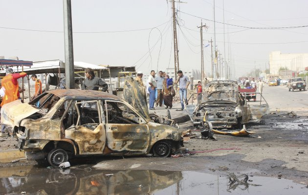 Residents gather at the site of a bomb attack in Basra