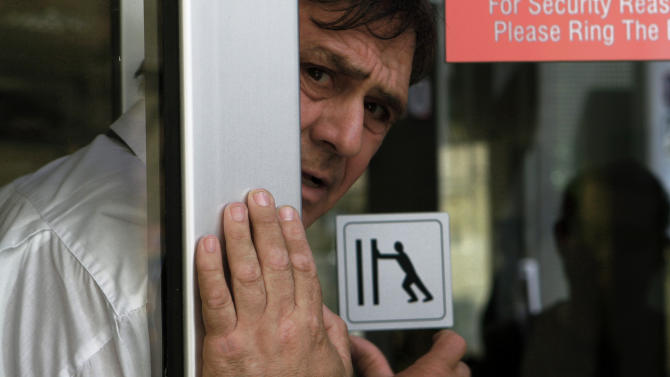 A private security officer stands at a main door of a bank as a man adjust the door as he waits outside of a branch of Laiki bank in central capital Nicosia, Cyprus, on Friday, March 29, 2013. Banks in Cyprus are open for normal business for the second day, but with strict restrictions on how much money their clients can access, after being shut for nearly two weeks to prevent people from draining their accounts as the country's politicians sought a way out of an acute financial crisis. (AP Photo/Petros Karadjias)
