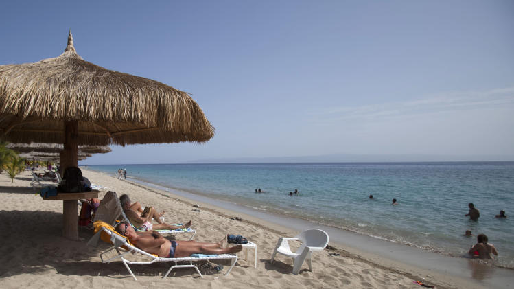 In this June 29, 2013, tourists rest seaside while others wade in the ocean waters at the Club Indigo beach resort in Montrouis, Haiti. While many in Haiti welcome anything that can create jobs, some critics are questioning the government's priority of trying to attract high-end tourists at a time when the country faces so many other problems, such as high unemployment, a deadly cholera outbreak and lack of housing for people displaced by the earthquake more than three years ago. (AP Photo/Dieu Nalio Chery)