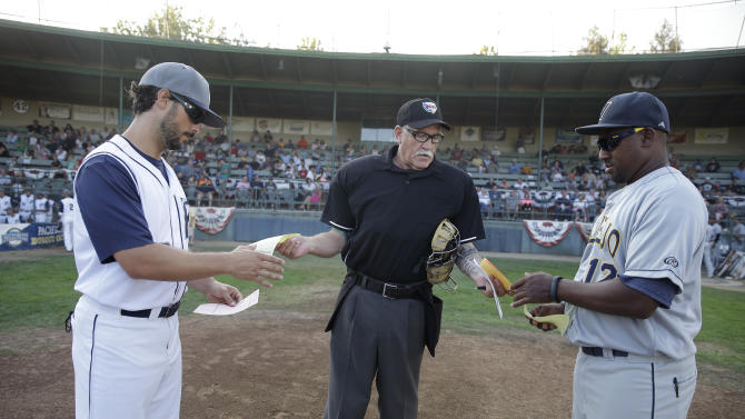 Home plate umpire Dean Poteet, center, exchanges lineups with San Rafael Pacifics manager Matt Kavanaugh, left, and Vallejo Admirals manager Gary Templeton II, right, before the start of an independent minor league baseball game Tuesday, July 28, 2015, in San Rafael, Calif. On Tuesday night, a computer system stood in for pitch calls in what is considered to be the first professional game without the umpire making those decisions. A full umpiring crew will be there for everything else.(AP Photo/Eric Risberg)