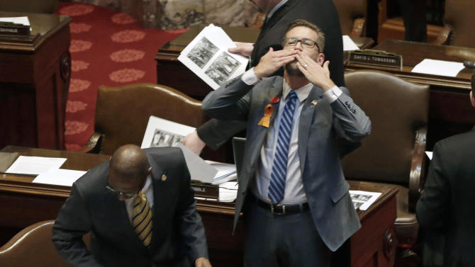 Sen. Scott Dibble, an openly gay lawmaker who sponsored the Senate's gay marriage bill, throws a kiss toward the gallery as the Senate prepared to debate the issue, Monday, May 13, 2013 in St. Paul, Minn. The bill passed the Minnesota House last week. (AP Photo/Jim Mone)