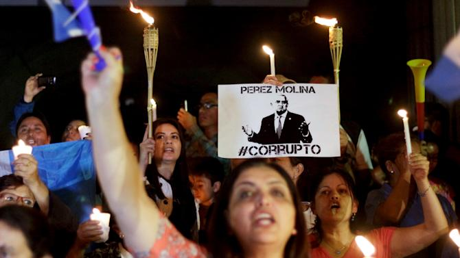 Demonstrator holds up sign during protest demanding resignation of President Perez Molina, in Guatemala City