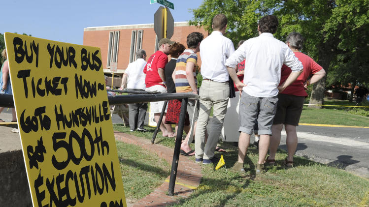In this photo taken June 12, 2013, death penalty opponents gather outside the Huntsville Unit before the execution of confessed killer Elroy Chester in Huntsville, Texas. Chester, convicted of the 1988 the fatal shooting of Port Arthur firefighter Willie Ryman III, was the 499th prisoner to be executed in Texas since 1982. (AP Photo/Pat Sullivan)