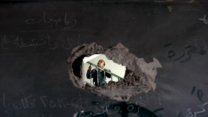 A Palestinian schoolgirl is seen through a hole in a blackboard days after an Israeli strike hit a school in Gaza City, Monday, Nov. 26, 2012. Israel launched its offensive on Nov. 14 in a bid to halt months of Palestinian rocket attacks. It says it inflicted heavy damage on Gaza militants, but the territory's armed groups fired hundreds of rockets into Israel before a cease-fire was declared Wednesday, Nov. 21, 2012.(AP Photo/Adel Hana)