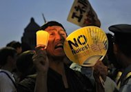 "A protester holding a candle and a fan displaying the words ""No Nukes"" shouts slogans as he takes part in a rally in front of Japan's parliament, to demonstrate against the use of nuclear power following the 2011 Fukushima atomic crisis, in Tokyo"
