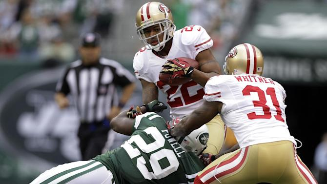 San Francisco 49ers cornerback Carlos Rogers (22) runs the ball back after recovering a fumble while New York Jets running back Bilal Powell  tackles him and teammate  Donte Whitner (31) blocks during the first half of an NFL football game Sunday, Sept. 30, 2012, in East Rutherford, N.J. (AP Photo/Kathy Willens)