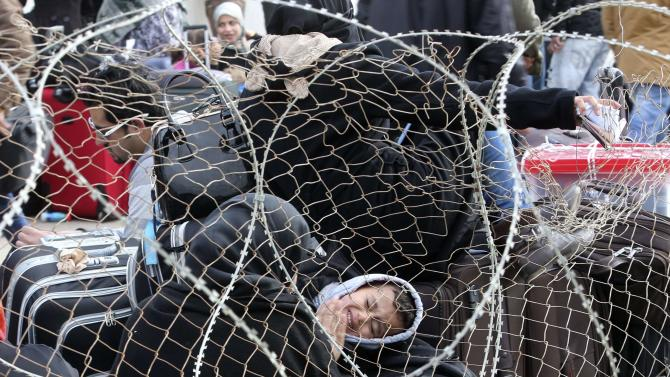 Palestinians, hoping to cross into Egypt, are pictured through a fence as they wait at the Rafah crossing between Egypt and the southern Gaza Strip