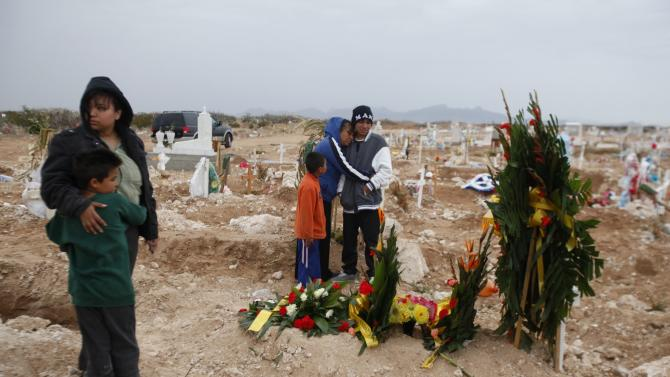 Relatives of late 16-year-old Ivan stand next to his grave after a funeral service at a cemetery in Ciudad Juarez