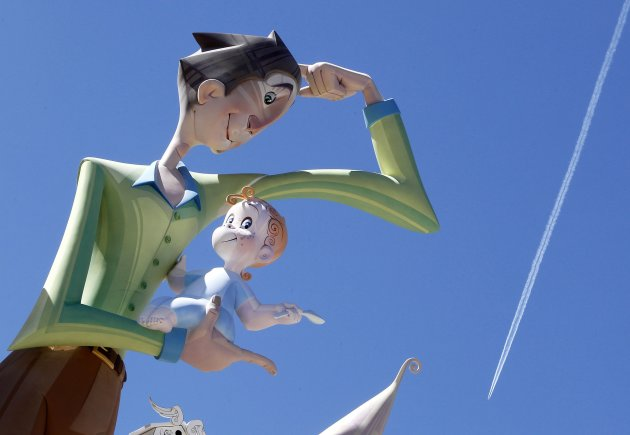 "An aeroplane flies above giant figures of a monument ahead of the ""Fallas"" festival in Valencia"