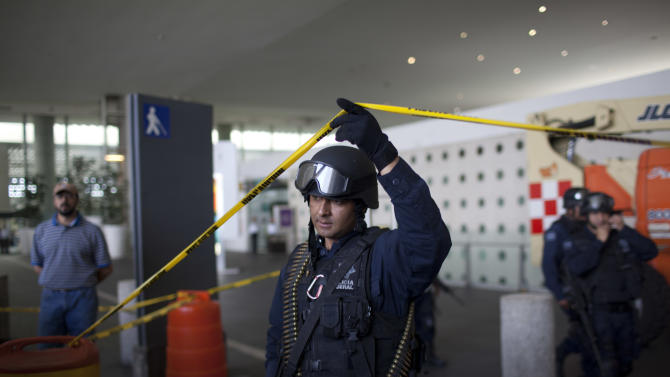 A federal police officer lifts a strip of crime scene barrier tape, as he leaves a marked-off area of the Mexico City's International Airport, where a shooting occurred around the food court at Terminal 2, Monday, June 25, 2012. Men wearing what appeared to be police uniforms opened fire in a food court at Mexico City's international airport on Monday, killing three federal policemen on an anti-drug mission. Two officers died at the scene and another died later of his wounds at a local hospital. (AP Photo/Alexandre Meneghini)